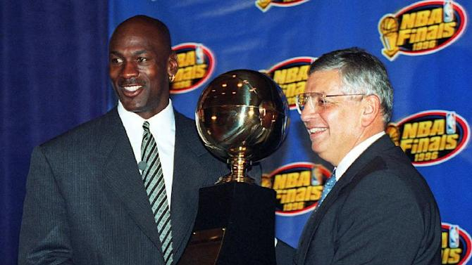 In this June 18, 1996, file photo, Chicago Bulls' Michael Jordan, left, receives the NBA Finals Most Valuable Player trophy from Commissioner David Stern during a ceremony in Chicago. Stern is not in the Hall of Fame, he never played in an All-Star game and he is about a foot shorter than most NBA stars. But try to find an NBA legacy more lasting than Stern's, who is retiring Saturday, Feb. 1, after exactly 30 years on the job