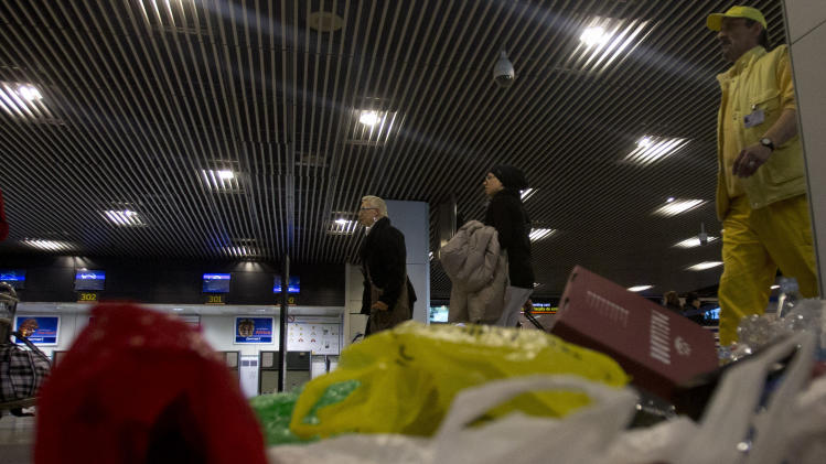 Passengers and a worker walk past accumulated garbage during a cleaners strike, at Barajas international airport in Madrid, Monday Jan. 28, 2013. Battling to reduce a swollen deficit and avoid a bailout, the year-old conservative government has brought major financial and labor reforms and applied severe cutbacks in wages and spending but so far the economy has shown few signs of recovery. (AP Photo/Paul White)