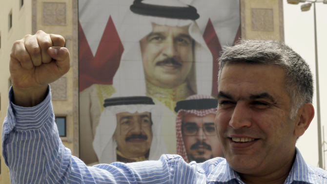 Bahraini human rights activist Nabeel Rajab gestures as he leaves a Manama, Bahrain, police station Monday, May 28, 2011. The image on the building behind him shows, clockwise from top, King Hamad bin Isa Al Khalifa, Crown Prince Salman bin Hamad Al Khalifa and Prime Minister Khalifa bin Salman Al Khalifa. The prominent Bahraini rights activist was released on bail Monday, more than three weeks after his arrest on charges linked to anti-government protests in the Gulf kingdom. (AP Photo/Hasan Jamali)