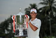 Matteo Manassero of Italy poses with the winner&#39;s trophy on day four of the Singapore Open at the Sentosa Golf Club in Singapore, in a handout photo provided by World Sport Group on November 11, 2012. Manassero holed a 12-foot eagle putt on the third play-off hole to claim a dramatic victory over South Africa&#39;s Louis Oosthuizen at the Singapore Open on Sunday