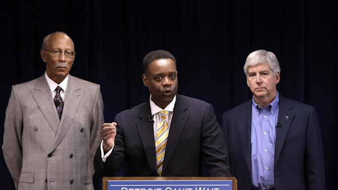 Kevyn Orr, center, speaks at a news conference as Detroit Mayor Dave Bing, left, and Gov. Rick Snyder listen in Detroit, Thursday, March 14, 2013. Snyder announced that he had chosen Orr, a partner in the Cleveland-based law and restructuring Jones Day firm, as Detroit's emergency manager. Snyder's already declared a financial emergency in Detroit, saying local officials lacked a plan to solve it. (AP Photo/Paul Sancya)