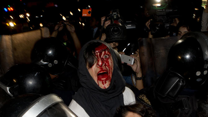 A protester injured in a scuffle with police shouts out his name as he and a woman are detained in Mexico City, Thursday, Feb. 26, 2015. The pair, and other protesters who had taken part in a march marking the fifth month of the disappearance of 43 students from a rural teachers college, clashed with police after they were prevented from entering the subway. The man shouts his name out of fear that he will disappear once in custody. (AP Photo/Eduardo Verdugo)