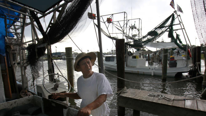 In this May 16, 2012, photo, Tuna Pham, a shrimper, talks as he works on his idle boat in Lafitte, La. The mood is gloomy on the hard-working shrimp and crab docks of this gritty fishing town in the Barataria estuary, a traditional seafood basket for New Orleans, as the second full year of fishing since BP's catastrophic oil spill kicks into high gear. Usually folks are upbeat and busy in May, the month when shrimpers get back to work in Louisiana's rich waters. But this spring, catches are down, docks are idle and anxiety is growing that the ill effects of the BP spill may be far from over. (AP Photo/Gerald Herbert)