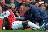 Arsenal's French defender Bacary Sagna receives treatment after picking up an injury during the English Premier League football match between Arsenal and Norwich City at The Emirates Stadium in north London