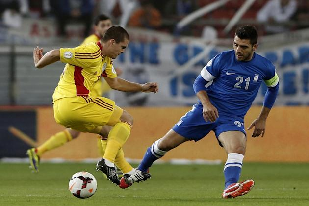 Greece's Kostas Katsouranis, right, challenges for the ball with Romania's Alexandru Bourceanou during their World Cup qualifying playoff first leg soccer match at the Karaiskaki stadium in the port o
