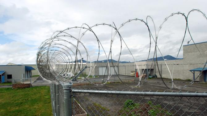 FILE - This March 18, 2011 file photo shows razor wire circling the inmate garden at the Josephine County Jail in Grants Pass, Ore. The failure of a $12 million levy has forced layoffs of 70 people in the Josephine County Sheriff's office, requiring the release of about 90 inmates. With only 28 uniformed and civilian staff left, the sheriff's office will only have enough jail deputies guard 30 inmates. (AP Photo/Jeff Barnard)