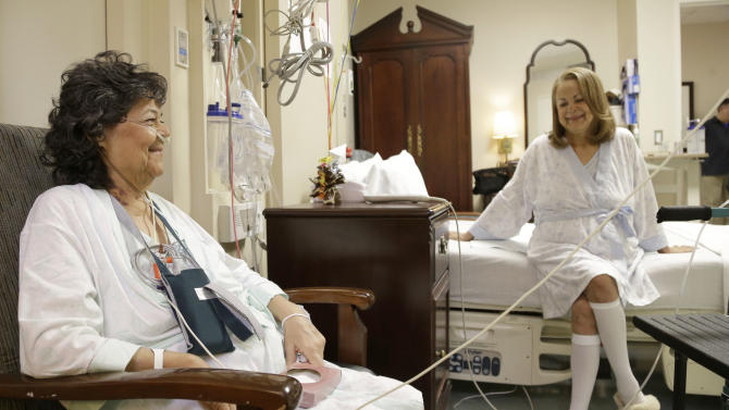 In this Jan. 14, 2014 photo, Irma Myers-Santana, left, and her sister Anna Williamson visit in Williamson's hospital room in Houston. Earlier this month the sisters ended up in the same operating room, each getting one lung from the same donor. (AP Photo/Pat Sullivan)