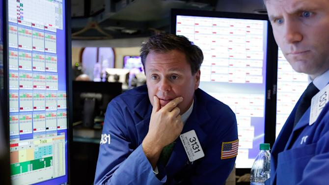 Specialist Matthew Cheslock, left, works on the floor of the New York Stock Exchange, Tuesday, May 26, 2015. Stocks are opening lower on Wall Street as traders return from the Memorial Day holiday in the U.S. (AP Photo/Richard Drew)