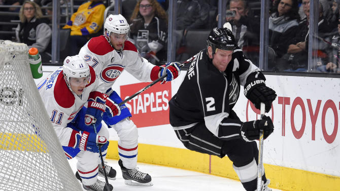 Los Angeles Kings defenseman Matt Greene, right, moves the puck as Montreal Canadiens right wing Brendan Gallagher, left, and center Alex Galchenyuk give chase during the first period of an NHL hockey game, Thursday, March 5, 2015, in Los Angeles. (AP Photo/Mark J. Terrill)