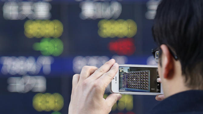 A man takes a picture of an electric stock price display of a securities firm with a smartphone in Tokyo Tuesday, Jan. 29, 2013. Asian stock markets posted modest gains Tuesday as the feel-good factor lingered from near-record highs on Wall Street and signs of an upswing in U.S. manufacturing.  (AP Photo/Koji Sasahara)