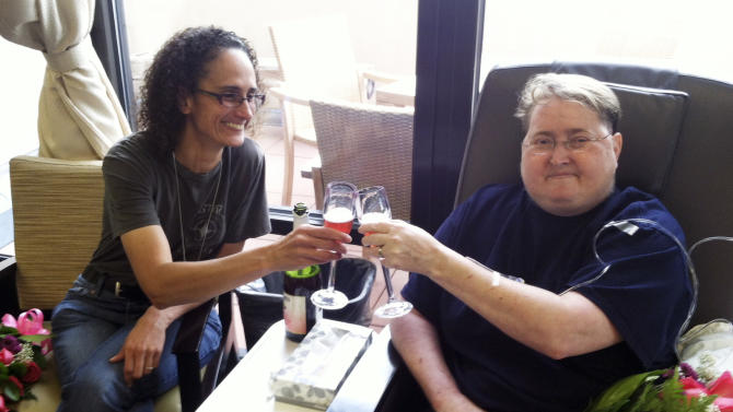 This image provided by the ACLU of New Mexico shows Angelique Neuman, left and Jen Roper, both of Pojoaque, N.M., celebrating at the Christus St. Vincent Regional Medical Center in Santa Fe, N.M., after receiving a same-sex marriage license. Roper, who is dying of brain cancer, was part of a recent lawsuit to get New Mexico courts to recognize same-sex marriages. Santa Fe County was ordered to grant same-sex licenses Friday, Aug. 23, 2013. (AP Photo/ACLU of New Mexico)