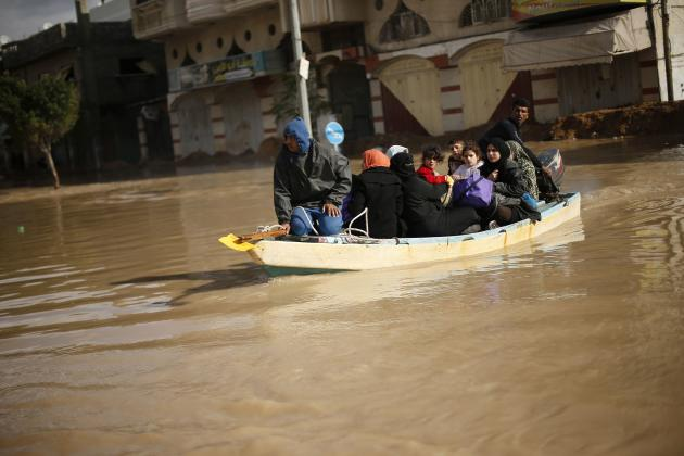 Palestinians travel on a boat after heavy rains in Gaza City