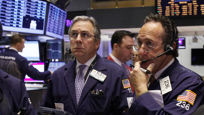 Traders Thomas Kay, left, and Steven Kaplan work on the floor of the New York Stock Exchange, Monday, April 9, 2012. Stocks pulled back sharply at the open as Wall Street got its first chance to react to a slowdown in hiring in the United States in March. (AP Photo/Richard Drew)