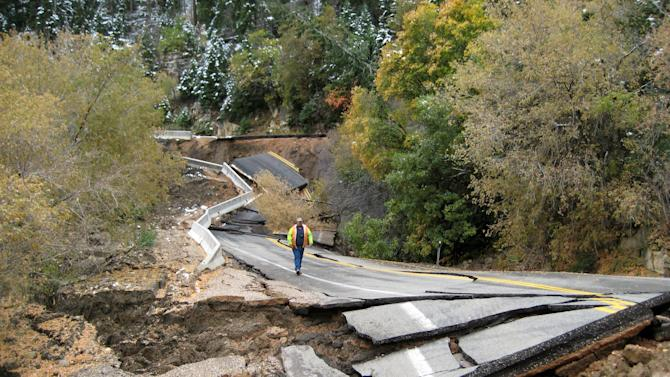 In this photo dated Saturday Oct. 8,2011 released  by the Utah Department of Transportation showing a road worker walking along destroyed state Route 14, a scenic road east of Cedar City in southwestern Utah often used by tourists traveling to Bryce Canyon National Park. Utah transportation officials have closed the state highway east of Cedar City after a massive landslide buried part of the roadway in about 100 feet of dirt and rock. (AP Photo/Utah Department of Transportation)