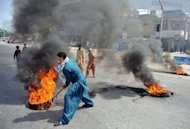 A Pakistani demonstrator drags burning tyres during a protest against an anti-Islam film in Rawalpindi. Fresh protests have erupted across the Muslim world against a US-made film and French cartoons mocking Islam, with violent demonstrations in Pakistan leaving at least 13 people dead