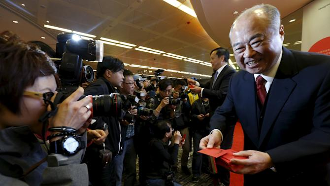 Hong Kong Exchanges and Clearing Ltd Chairman Chow Chung-kong and Chief Executive Charles Li offer red packets to journalists on the first day of trading after Lunar New Year holidays at the Hong Kong Stocks Exchange