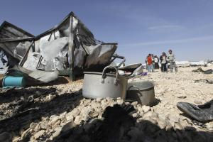 Syrian refugees stand near their damaged belongings …
