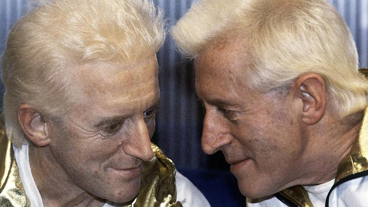 FILE - In this Dec. 17, 1986 file photo, Jimmy Savile, right, poses for photographers with a wax work model at Madame Tussauds museum in London. The BBC on Wednesday, Dec. 19, 2012 is set to publish the results of an independent review into the broadcaster's decision to shelve a news report on child sex abuse allegations against the late TV presenter Jimmy Savile. (AP Photo/John Redman, File)