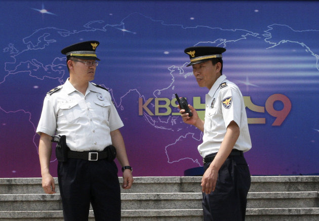 "South Korean police officers stand guard in front of the Korea Broadcasting System (KBS) building in Seoul, South Korea, Monday, June 4, 2012. North Korea's military warned Monday that troops have aimed artillery at the specific coordinates of South Korean media groups as Pyongyang threatened a ""merciless sacred war"" over alleged insults. (AP Photo/Ahn Young-joon)"