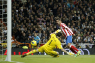 Atletico de Madrid's Adrian Lopez, right, scores against Real Madrid's Ilker Casillas during his Spanish La Liga soccer match at the Santiago Bernabeu stadium, in Madrid, Spain, Saturday, Nov. 26, 2011. (AP Photo/Daniel Ochoa de Olza)