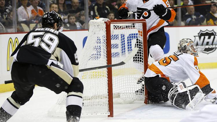 Pittsburgh Penguins' Jayson Megna (59) scores on Philadelphia Flyers goalie Steve Mason (35) during the second period of an NHL hockey game on Sunday, March 16, 2014, in Pittsburgh. (AP Photo/Keith Srakocic)
