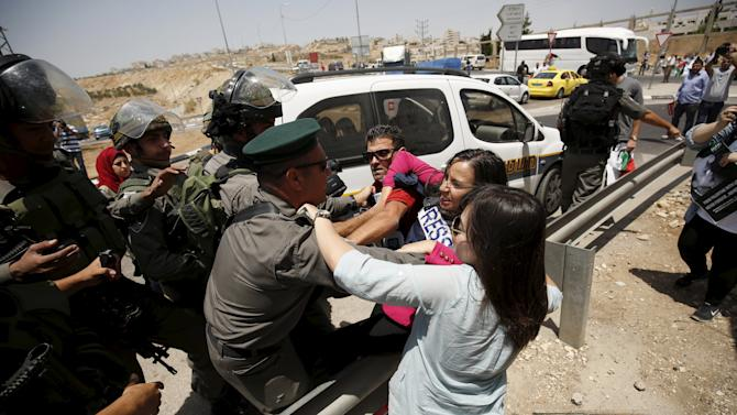 Palestinian journalists scuffle with Israeli border policemen during a protest near Ramallah