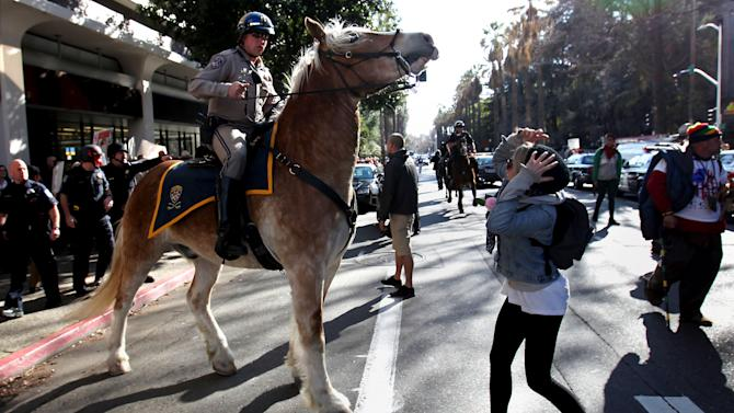 A mounted California Highway Patrol Officer moves a member of the Occupy movement away from  a pro-white group during a demonstration in Sacramento, Calif., Monday, Feb. 27, 2012. A clash erupted as California highway Patrol Officers and Sacramento city police officers were escorting members of a group called the South Africa Project to a parking garage following their protest outside the Capitol.(AP Photo/Rich Pedroncelli)
