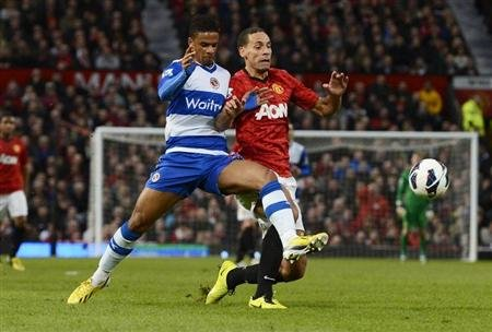 Manchester United's Ferdinand challenges Reading's McCleary during their English Premier League soccer match at Old Trafford in Manchester