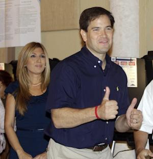 Florida Republican U.S. Senate candidate Marco Rubio gives two thumbs up after casting his vote as his wife Janette, left, looks on Tuesday, Nov. 2, 2010, in West Miami. (AP Photo/Alan Diaz)