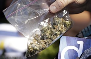 A man pulls out a bag of marijuana to fill a pipe at …