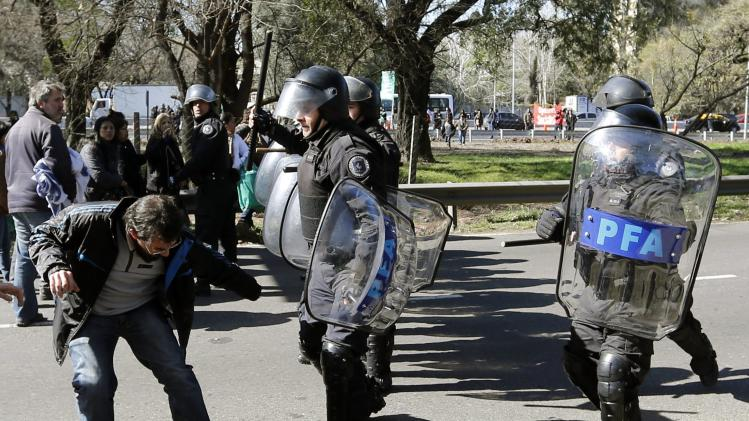 A demonstrator tries to avoid being hit by anti-riot policemen during a protest staged by state-run workers who were seeking to block a road in Buenos Aires