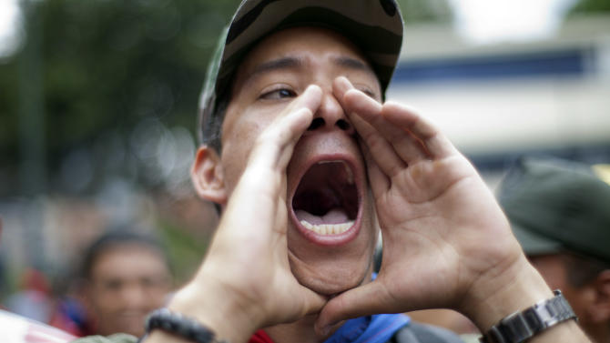 A 'Chavista' demonstrator shouts as supporters of President-elect Nicolas Maduro march in front of the National Electoral Council (CNE) in Caracas,Venezuela, Wednesday, April 17, 2013.  Opposition candidate Henrique Capriles has presented a series of allegations of vote fraud and other irregularities to back up his demand for a vote-by-vote recount for the presidential election. (AP Photo/Ramon Espinosa)