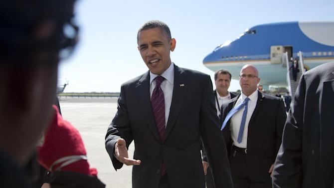 President Barack Obama greets people as he arrives at John F. Kennedy International Airport, Tuesday, Oct. 16, 2012, in New York, en rout to Hempstead, N.Y. and a presidential debate.  (AP Photo/Carolyn Kaster)