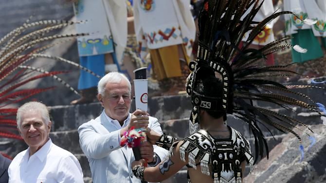 Chairman of the Toronto 2015 Pan-American Games organizing committee, Peterson (C) delivers the torch of the Pan American Games to a Mexican dressed in prehispanic costumes during the Ceremony of the Ignition of the New Fire, at the pyramids of Teotihuacan