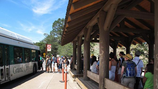 In this Wednesday, Aug. 19, 2015 photo, tourists at Grand Canyon National Park in northern Arizona wait for a shuttle bus. Grand Canyon and other big national parks are seeing more visitors than usual this year, partly driven by good weather, cheap gas and marketing campaigns. (AP Photo/Felicia Fonseca)