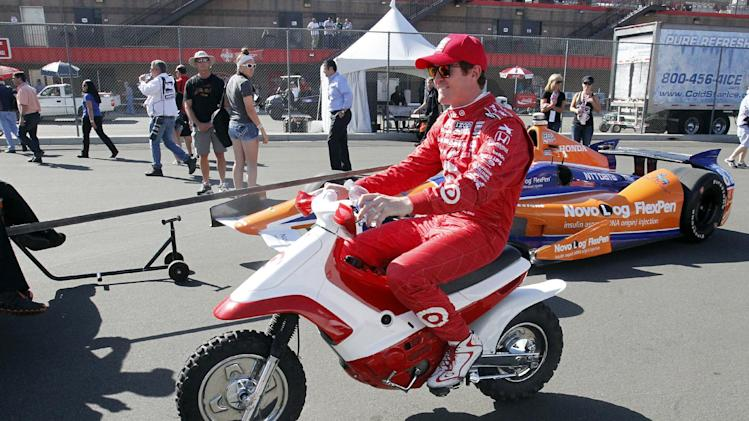 Driver Scott Dixon, of New Zealand, rides on a scooter in the pit road prior to a practice round for the MAVTV 500 IndyCar World Championship at Auto Club Speedway, Friday, Oct. 18, 2013 Fontana, Calif. (AP Photo/Alex Gallardo)