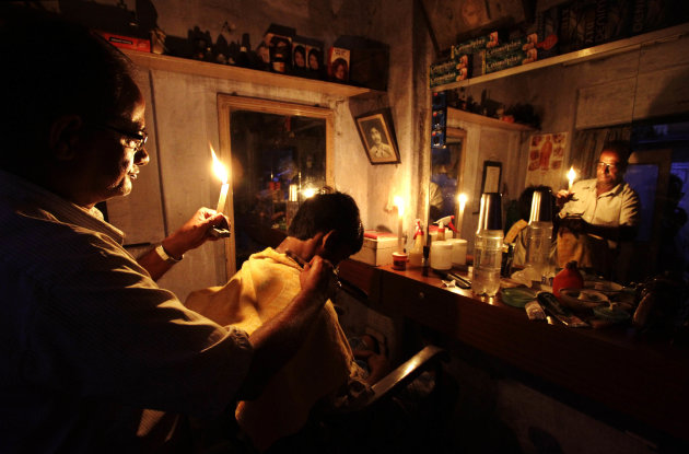 An Indian barber holding a candle,  has a haircut for a customer at his shop in Kolkata, India, Tuesday, July 31, 2012. India's energy crisis cascaded over half the country Tuesday when three of its r