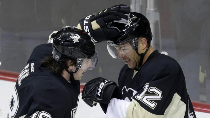 Pittsburgh Penguins right wing Jarome Iginla (12) celebrates his first goal as a Penguin with Pittsburgh Penguins left wing James Neal (18) in the first period of an NHL hockey game in Pittsburgh against the Buffalo Sabres, Tuesday, April 2, 2013. (AP Photo/Gene J. Puskar)