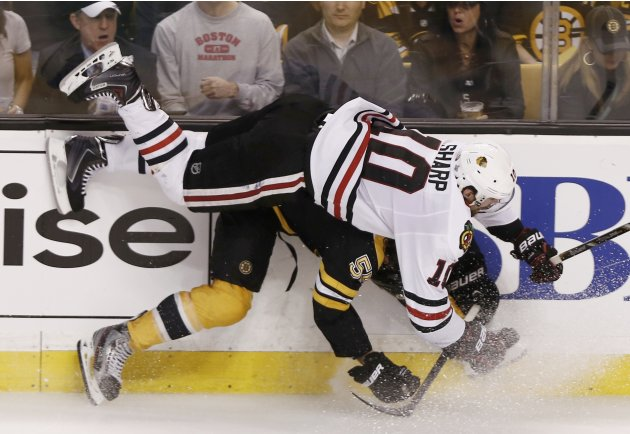 Blackhawks' Sharp flies over Bruins' Boychuk during the third period in Game 4 of their NHL Stanley Cup Finals hockey series in Boston