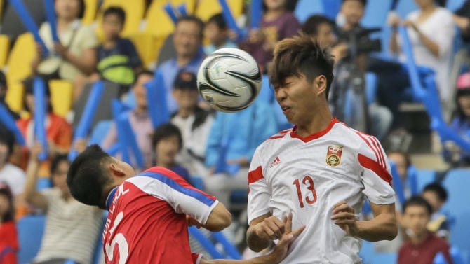 China's Fu Huan, right, fights for the ball with North Korea's  Jang Kuk Chol during their first round soccer match at the 17th Asian Games in Incheon, South Korea, Monday, Sept. 15, 2014. (AP Photo/Dita Alangkara)