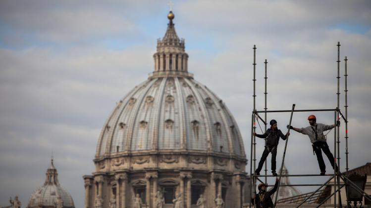 Workers sets up a stage for the media next to St Peter's Square ahead of Pope Benedict XVI's last public audience Wednesday, at the Vatican, Tuesday, Feb. 26, 2013.  Pope Benedict XVI has changed the rules of the conclave that will elect his successor, allowing cardinals to move up the start date if all of them arrive in Rome before the usual 15-day transition between pontificates. Benedict signed a legal document, issued Monday, with some line-by-line changes to the 1996 Vatican law governing the election of a new pope. It is one of his last acts as pope before resigning Thursday. (AP Photo/Oded Balilty)