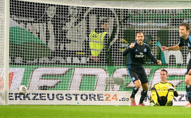 In this picture taken Friday Nov. 29, 2013, Wolfsburg's goalie  Diego Benaglio  sits on the pitch as Hamburg's Pierre-Michel Lasogga, left, celebrates a goal, during the German Bundesliga soccer match
