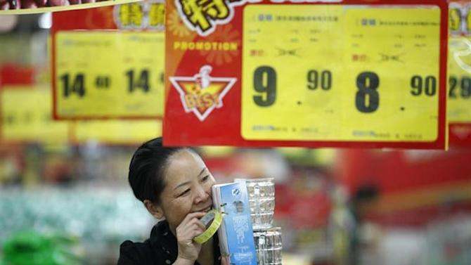 A woman bites off a piece of sellotape at a supermarket in Huaibei, Anhui province, October 14, 2013. REUTERS/Stringer