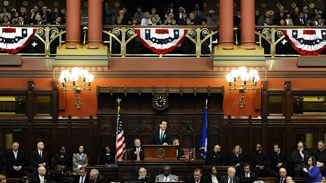 """Connecticut Gov. Dannel P. Malloy, center, at podium, speaks to members of the House and the Senate in his State of the State address at the Capitol in Hartford, Conn., Wednesday, Jan. 9, 2013. Malloy urged state lawmakers Wednesday to work with him to prevent future tragedies like the Sandy Hook Elementary School shooting, but stressed that """"more guns are not the answer.""""  Legislators also must grapple with a projected deficit of about $1.2 billion. (AP Photo/Jessica Hill)"""