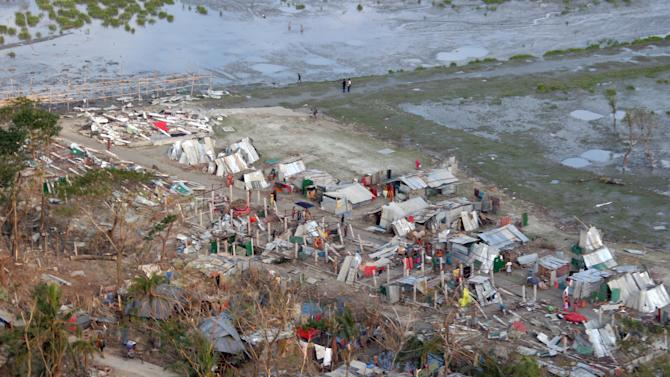 This Nov. 24, 2007 file photo provided by the U.S. Navy, shows an aerial view of shows temporary shelters and damage to a village and infrastructure following Cyclone Sidr, which swept into southern Bangladesh Nov. 15, as seen from a U.S.Marine  Corps aid helicopter. Extreme storms, droughts and heat waves are getting so much worse because global warming that the world has to prepare for an unprecedented onslaught of deadly and costly weather disaster, an international panel of experts says. (AP Photo/Navy-Marine Corps, Sgt. Ezekiel R. Kitandwe, File)