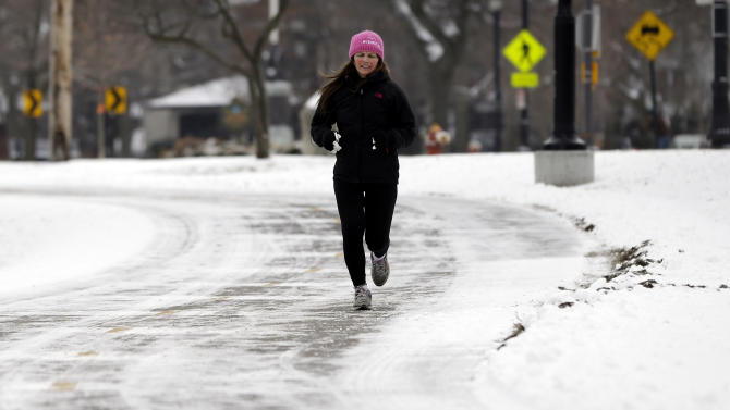 A jogger runs along a snow-covered street in Evanston, Ill., Friday, Jan. 25, 2013. The 1.1 inches that settled on Windy City streets and sidewalks marked the latest first seasonal snowfall of at least an inch in the Midwest metropolis since at least 1884, when records were first kept, National Weather Service forecaster Matt Friedlein said. The previous record was set on Jan. 17, 1899. Friday also broke Chicago's longest streak of consecutive days without an inch of snow. The city went 335 days, or about 11 months, without at least an inch, Friedlein said. (AP Photo/Nam Y. Huh)