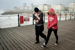 Strong winds blow two girls as they walk on Brighton…