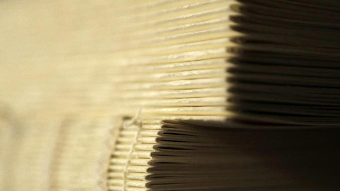 Volumes of the King James Bible that were transcribed by Phillip Patterson wait to be bound and covered on Tuesday, April 30, 2013, in Philmont, N.Y. (AP Photo/Mike Groll)
