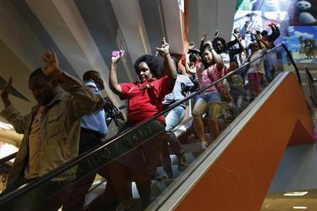 Civilians escape an area at the Westgate Shopping Centre in Nairobi September 21, 2013. REUTERS/Siegfried Modola