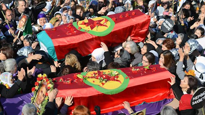People carry the coffins, covered with PKK flags, of three Kurdish activists as tens of thousands of people gather for their funeral in Diyarbakir, sourtheastern Turkey, Thursday, Jan. 17, 2013. The three women activists, including a founding member of the outlawed Kurdistan Workers' Party, or PKK, were found shot dead in Paris last week at a time when Turkey is holding peace talks with the rebels' jailed leader. Many believe the killings may be an effort to derail the talks. (AP Photo)